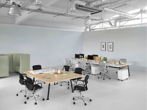 An open work area featuring a Memo meeting table and six Memo benching surfaces with light grey Aeron office chairs.
