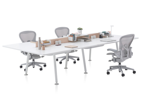 A white Memo project table with light grey Aeron office chairs.