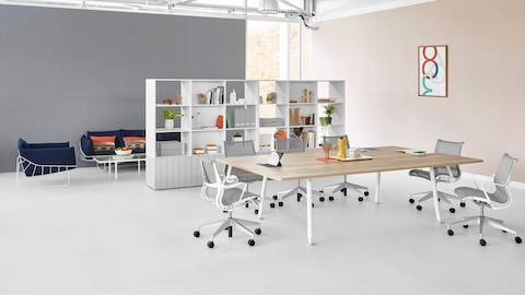 A meeting space featuring a Memo rectangular table with light grey Setu office chairs and bookcases in the background.