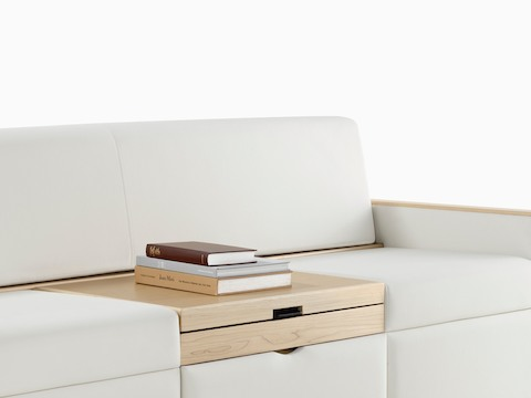 Partial view of a two-seat Merge Flop Sofa for healthcare guests, showing books atop the lowered centre table.