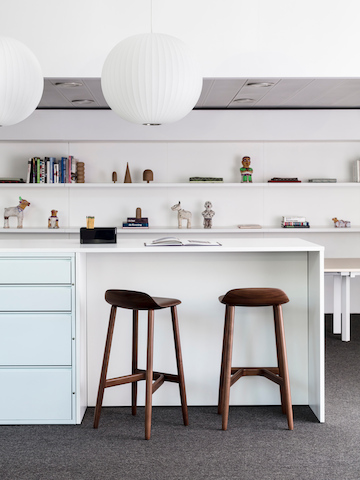 Light blue Meridian storage unit with standing-height worktop and two wooden crosshatch stools.