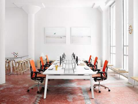 A bright work environment with orange Mirra 2 office chairs and other stools and benches.