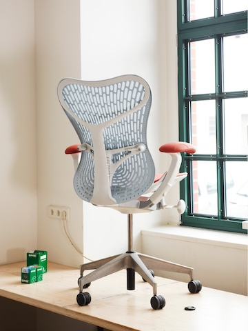 A blue Mirra 2 office chair, viewed from the rear and set close to a window.