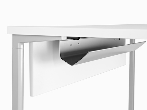 A white work surface equipped with a Modesty Panel and cable management trough.