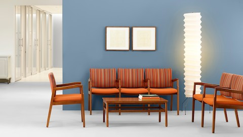 A healthcare waiting area including three-seat and two-seat Monarch Multiple Seating with orange upholstery and intervening arms.