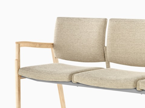 Partial view of beige Monarch Multiple Seating, showing a sculpted wood arm and memory foam seat.