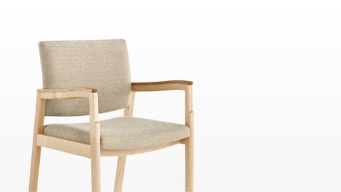 Angled view of a Monarch Multiple Seating chair with beige upholstery and a solid maple frame.