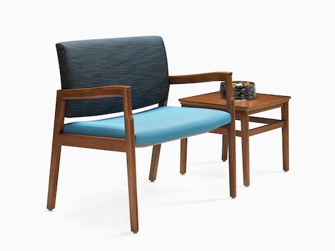 A Monarch Plus chair with a wide seat and two shades of blue upholstery next to a square occasional table.