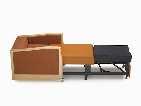 Profile view of an orange Monarch Sleep Chair converted into a sleep surface for healthcare guests.