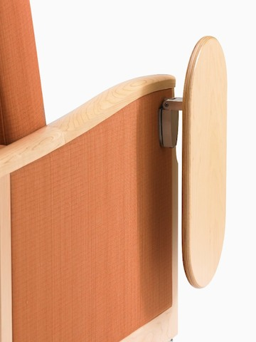 Close view of an optional tablet table attached to the side of an orange Monarch Sleep Chair.