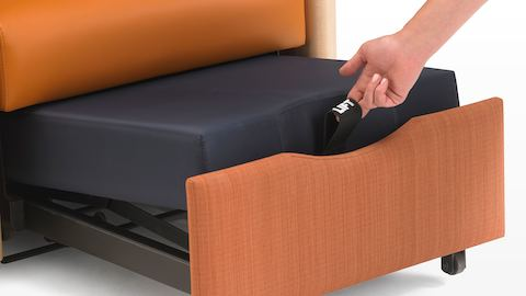 A hand pulls a strap to convert a Monarch Sleep Chair into a sleep surface.