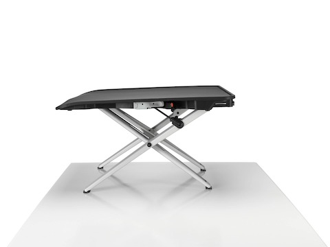 A back view of a Monto Sit-Stand Riser in a closed position and paired with a large black curved screen and white Ollin Monitor Arm.
