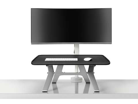 A front view of a Monto Sit-Stand Riser in a raised position and paired with a large black curved screen on a white Ollin Monitor Arm with an extended height clamp.