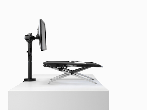 A back angled view of Monto Sit-Stand Riser paired with a black curved screen and Ollin Monitor Arm.