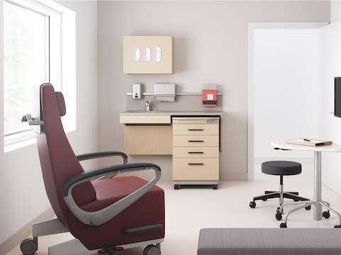 An exam room setting featuring Mora casework in an ash wood finish with a supply cart, Intent Solution in an ash finish, a physician's stool in dark gray, an Ava recliner in a maroon upholstery, and a Riva bench in gray.