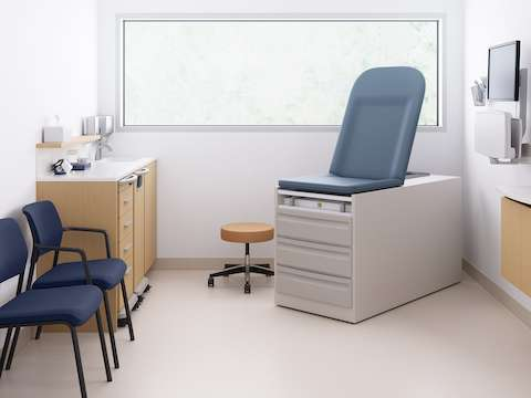 Mora casework in an oak finish with a mobile supply cart and a mobile trash cart with the caregiver work area, a technology support cabinet, two Verus Side Chairs in blue, a physician stool in tan, and an exam table.