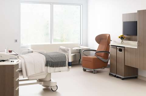 A patient room with a footwall of Mora casework with a trash cart and linen cart in medium brown wood finish, an Ava recliner in tan, a Palisade Flop Sofa in off white, a patient bed, with a Mora supply cart next to it.