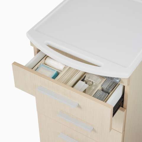 A close-up view of an open drawer with medical supplies in a Mora casework cart.
