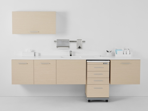 A Mora casework wall in a light ash finish consisting of one overhead storage cabinet and three lower supply cabinets with a supply cart docked within the casework.