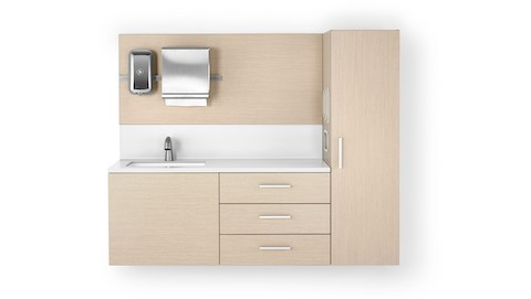 A Mora casework wall in an ash finish consisting of a 3-drawer storage case, a waredrobe, and a wall panel with a soap dispenser and paper towel dispenser. The white solid surface has an integrated sink and backsplash.
