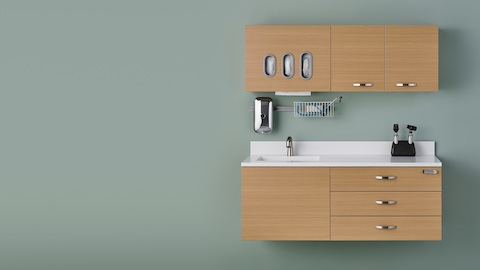Wall-mounted Mora System clinical casework, including drawers, a sink, overhead cabinets, and a glove dispenser.