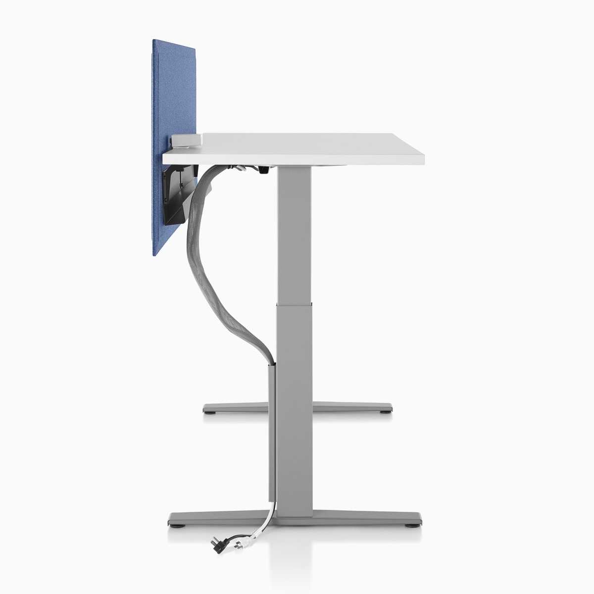 Side profile of Motia Sit-to-Stand Table with a cable management tray attached to the privacy screen and a cable manager attached along the base.