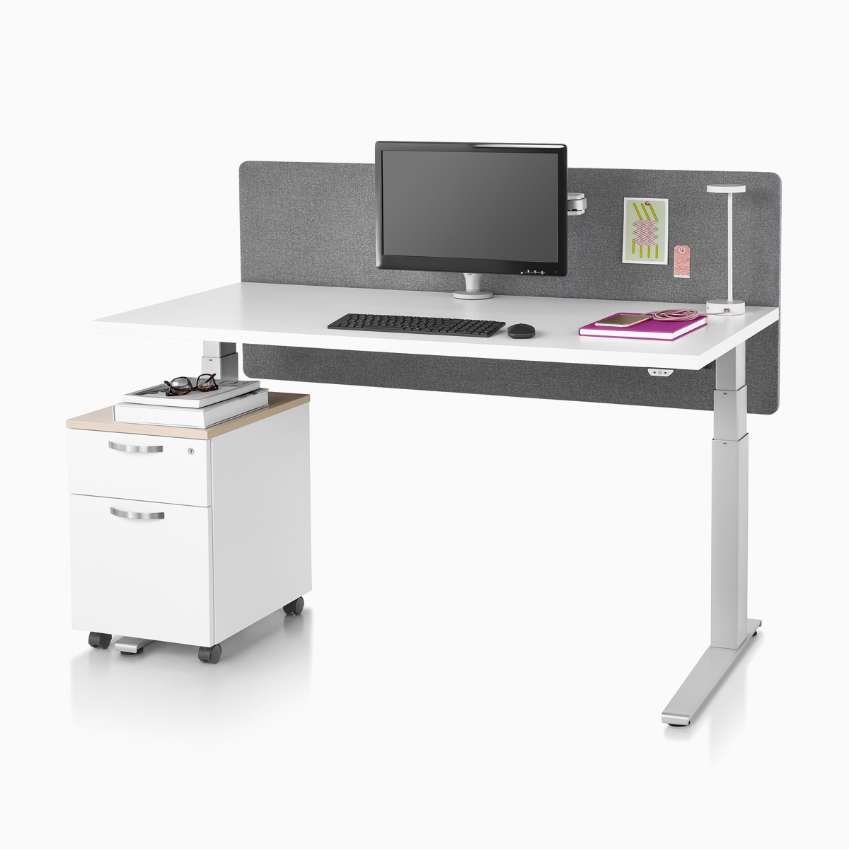 A Motia standing desk with a white top, metallic silver base, surface-attached privacy screen, desk lamp, and a Tu Wood pedestal.