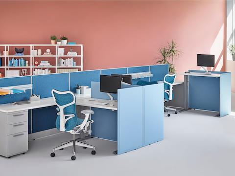 A white Motia Sit-to-Stand Table in a small workstation with low panels and a blue Mirra 2 office chair.