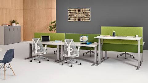 An open workstation featuring two white Motia Sit-to-Stand Tables, one at standing height and one at seated height.