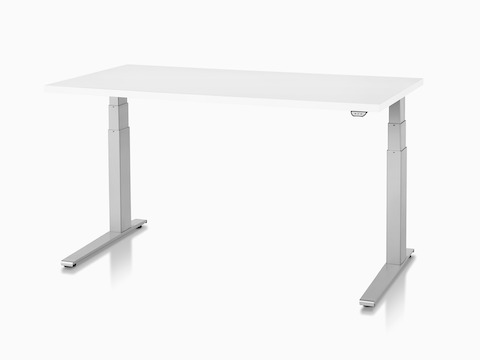 Angled view of an L-shaped Motia Sit-to-Stand Table with three white legs and the height-adjustment control visible under the surface.