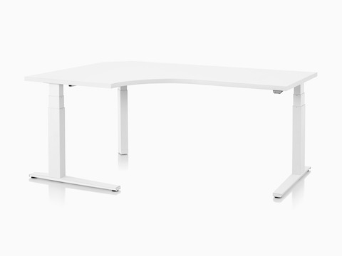 Viewed at an angle, a 90-degree extended corner Motia Sit-to-Stand Table, with a white work surface and T-leg base, at a seated height.