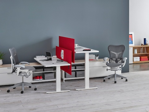 Red privacy screens separate two white Motia Sit-to-Stand Tables facing each other at seated and standing heights.