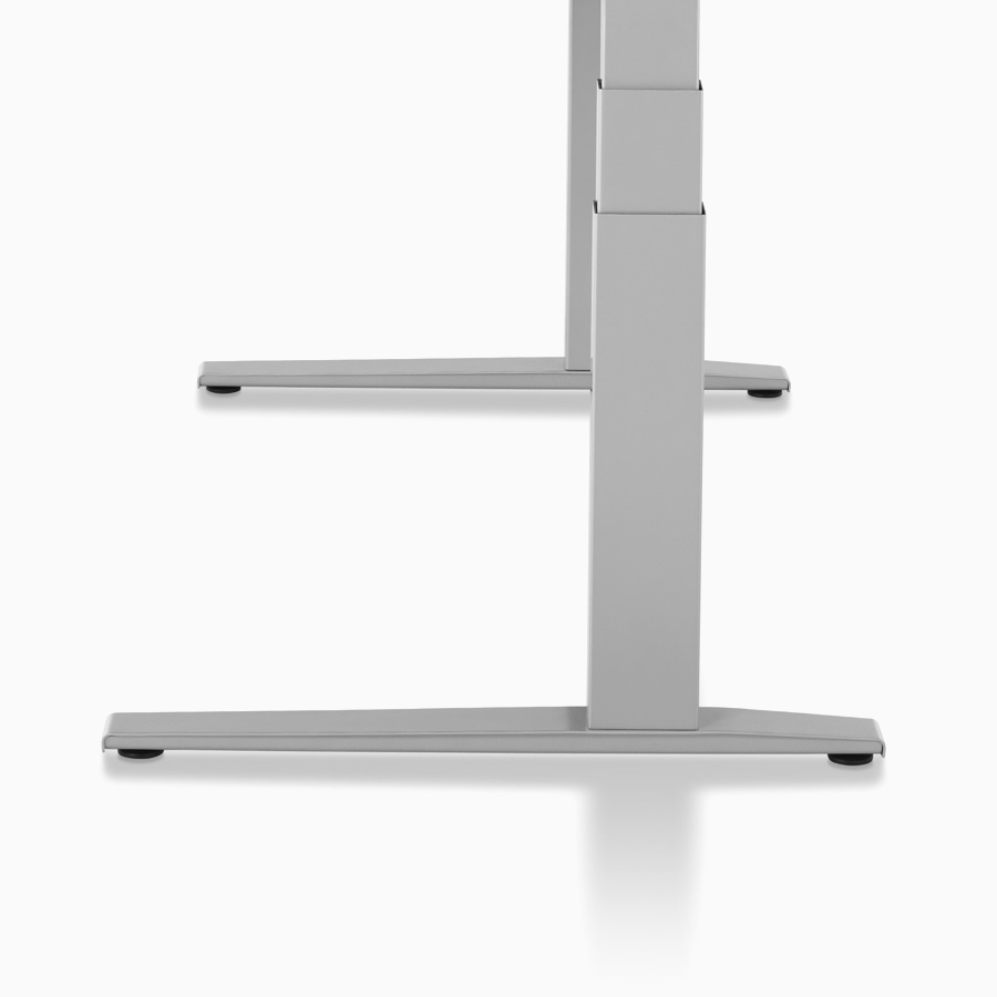 Side profile of a Motia Sit-to-Stand Table, with a white work surface and metallic silver C-leg base at a seated height.