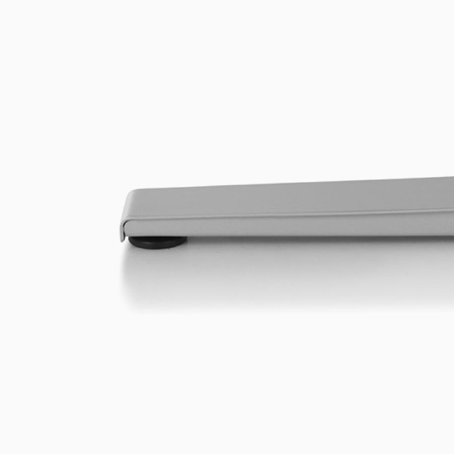 Close-up of Motia's metallic silver T-leg base.