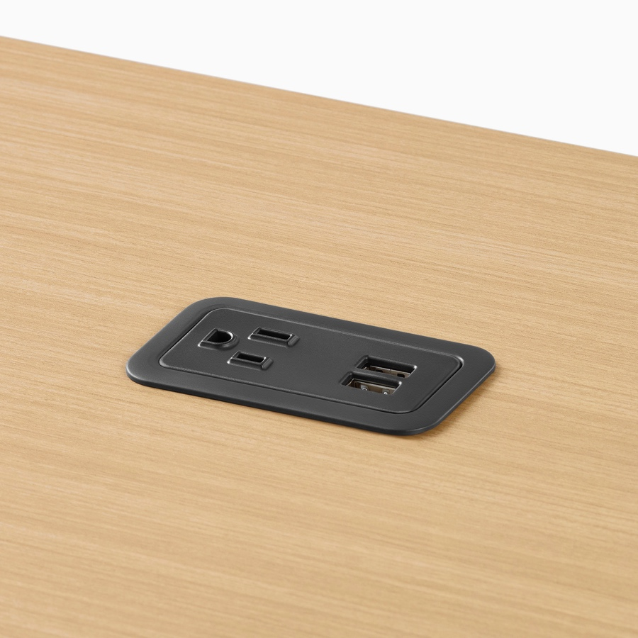 Close-up image of a black power outlet mounted within a wood Canvas Vista surface.