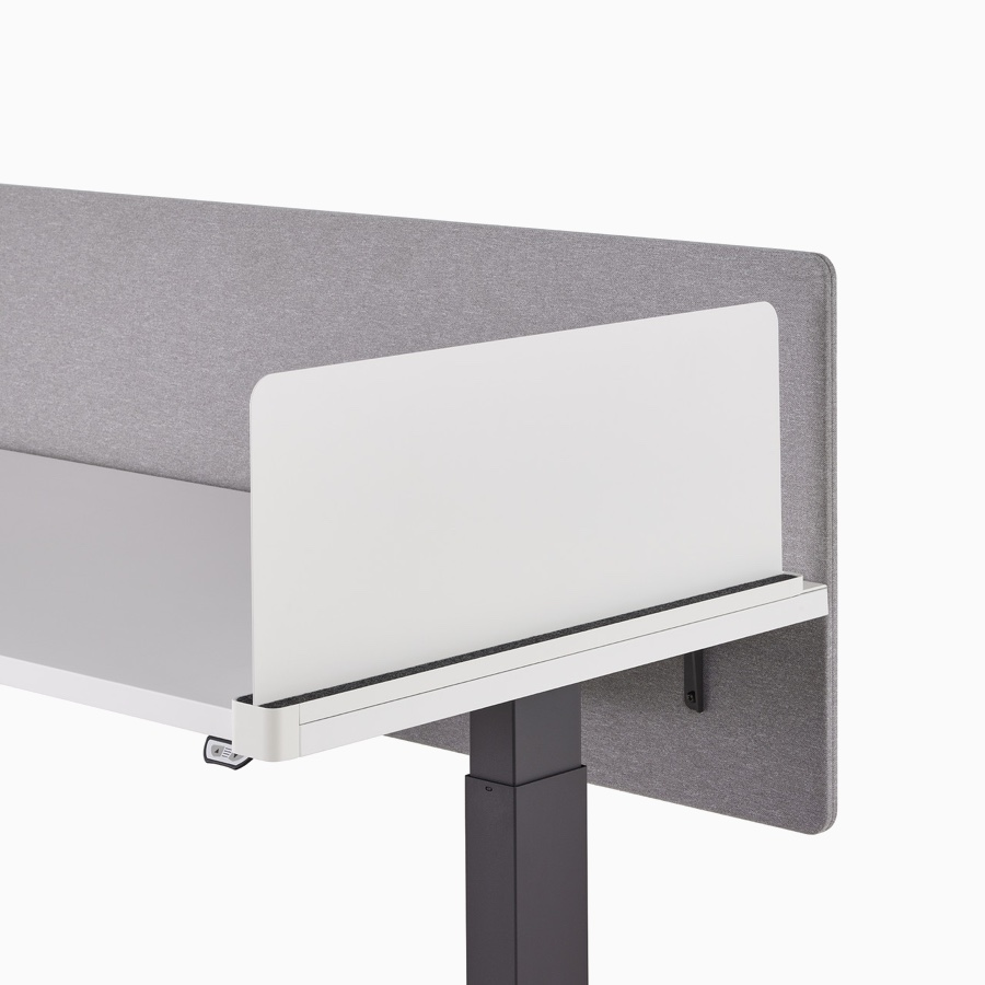 Close-up of a white Ubi slim metal delineation side screen with a surface attached gray privacy screen on a Motia Sit-to-Stand Table.