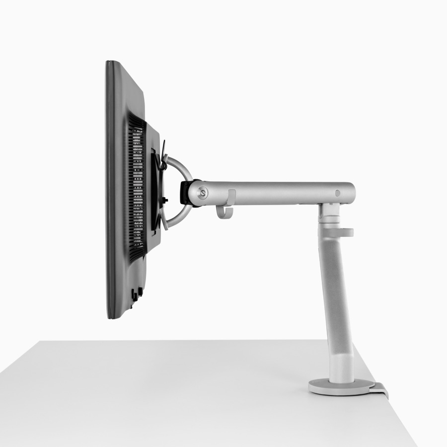 Side profile of a silver single Flo Monitor Arm holding a screen and attached to a white work surface.