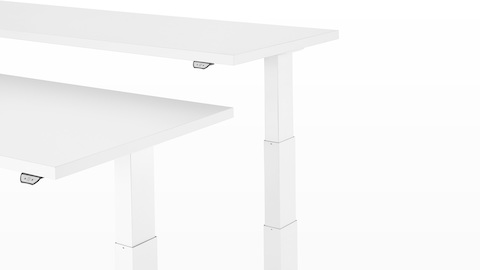 Angled view of two white Motia Sit-to-Stand Tables positioned at different heights with the adjustment mechanisms visible.