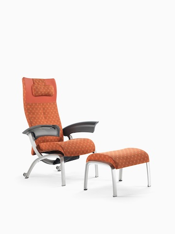 A patterned Nala Patient Chair and ottoman in shades of red and orange. Select to go to the Nala Patient Chair product page.