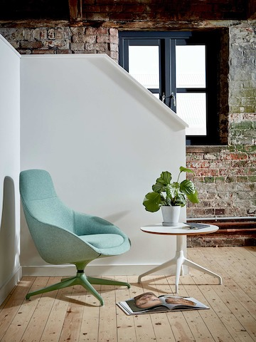 A green upholstered Always Lounge Chair fitted with a coordinating 4-star swivel base beside a white Ali Table, both from naughtone.