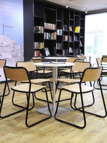 Black naughtone Bounce Chairs gathered in groups of 4 around white Ped Café Tables, a floor-to-ceiling bookshelf visible in the background.