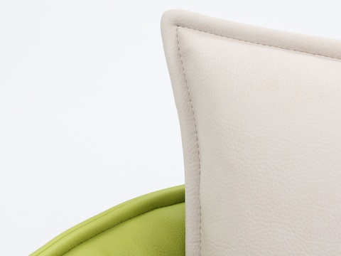 A close-up view of a naughtone Cloud Plain Sofa, where the cream leather of the seatback cushion rests against a chartreuse leather surround.