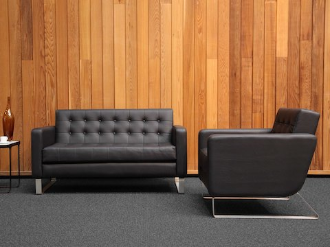 A side view of a black leather naughtone Clyde Club Chair next to a matching Clyde Sofa and Trace Side Table in a wood-paneled room.