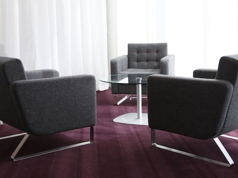 Three gray naughtone Clyde Club Chairs with deep red contrast buttons around a glass-top Ped Table in a room with white curtains and purple carpet.