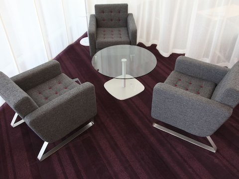 Three gray naughtone Clyde Club Chairs with red contrast buttons around a glass-top Ped Table in a carpeted room with curtains, viewed from above.