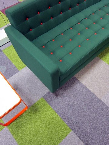 A green naughtone Clyde Sofa with orange contrast buttons beside an orange and white Trace Side Table on a green and purple carpet, viewed from above.