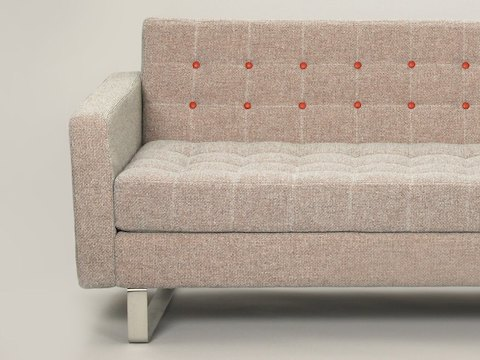A close-up front view of a textured gray-brown naughtone Clyde Sofa with rust-red contrast buttons.