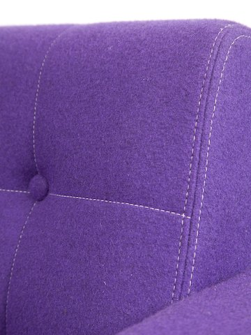 A detail view of white contrast stitching on the button-tufted seatback of a purple naughtone Clyde Sofa.