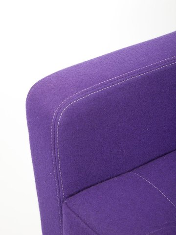 A detail view of white contrast stitching on the armrest and seat of a purple naughtone Clyde Sofa.