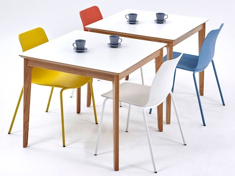 An angled, top-down view of two white naughtone Dalby Café Tables arranged with brightly coloured Polly Side Chairs and set with blue cups and saucers.